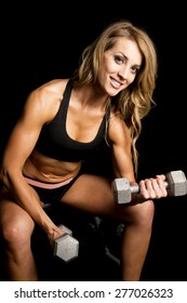 a fit woman with a smile on her face, sitting and doing arm curls with weights.