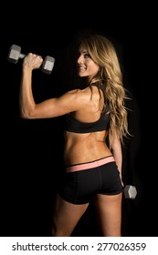 a fit woman with a smile on her face, looking over her shoulder with weights.
