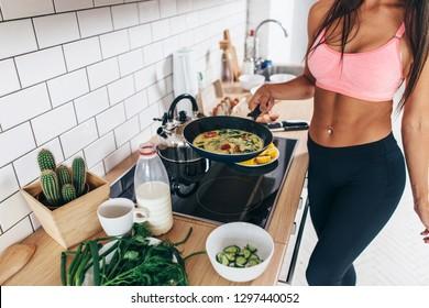 Fit woman standing at kitchen preparing healthy breakfast