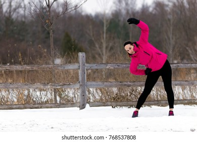 Fit woman stretches before jogging outdoors on a trail in winter.  Fit healthy lifestyle concept with beautiful young fitness model.