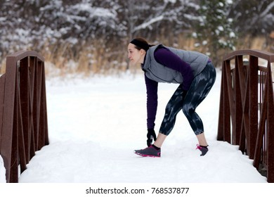 Fit woman stretches before running outdoors on a trail in winter.  Fit healthy lifestyle concept with beautiful young fitness model.