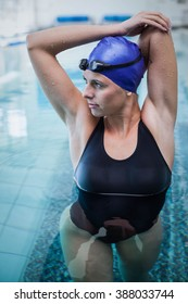 Fit woman stretching her arms in the water at the pool