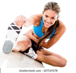 Fit woman stretching her leg to warm up - isolated over white background