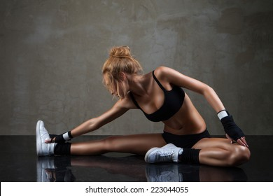 Fit woman stretching her leg to warm up over dark grey background