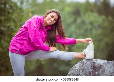Fit woman stretching her leg in the countryside
