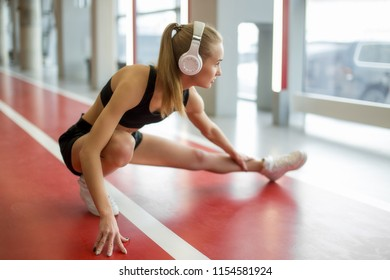 fit woman stretching her legs on track in gym. Fit female runner doing warmup