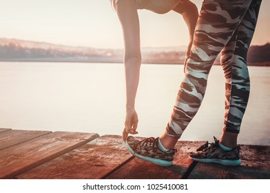 Fit woman stretching for running outdoors by the water