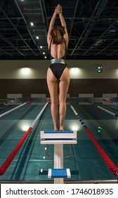 Fit woman is in swimming pool wearing black swimsuit