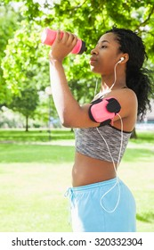 Fit woman taking a drink in the park