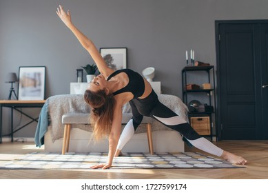 Fit woman trains at home, doing backbend.