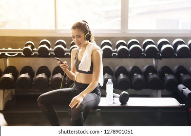 Fit woman using headphone and listening to music while sitting with relax after the training session in gym,Concept healthy and lifestyle,Female taking a break after exercise and workout