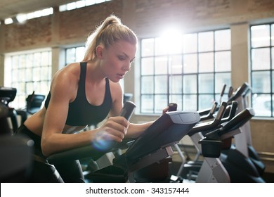 Fit woman working out on exercise bike at the gym. Indoor shot of a female doing fitness training on spinning bicycle at health club.