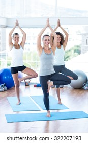 Fit women doing tree pose in fitness studio