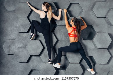 Fit women posing like a climber hanging on decorative wall