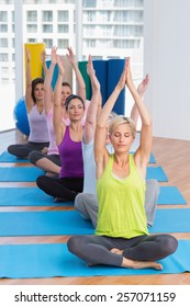 Fit women practicing yoga on exercise mats in fitness class