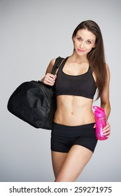 Fit women ready for the gym with kit bag and water bottle, studio shot.