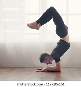 Fit yoga man doing advanced inversion and arm-balance exercises