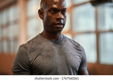 Fit young African American man in sportswear sweating while standing in a gym after a workout session