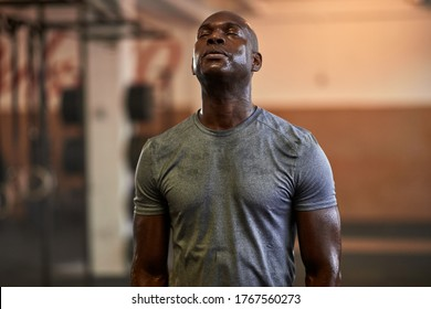 Fit young African American man standing with his eyes closed and sweating after a gym workout