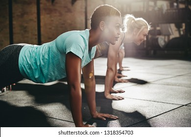 Fit young African American woman doing pushups on the floor of a gym with other people during a workout class