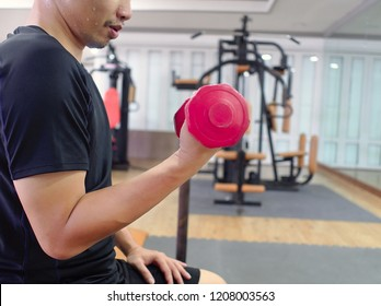 Fit young Asian man lifting dumbbell at sport gym. Fitness and workout concept