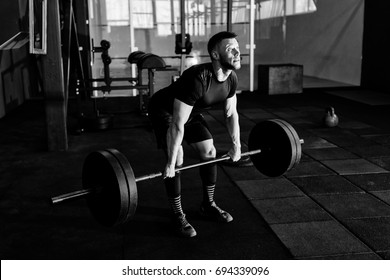 Fit young  athlete lifting the barbell in gym. Gym training