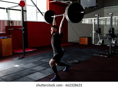 Fit young bearded athlete lifting the barbell in gym. Gym training. Full body length portrait