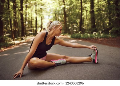 Fit young blonde woman in sportswear sitting on forest path doing warmup stretches before going for a run