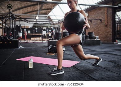 Fit young blonde woman in sportswear working out alone in a gym doing core exercises with a swiss ball