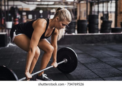 Fit young blonde woman in workout clothing preparing to lift heavy weights while working out alone in a gym