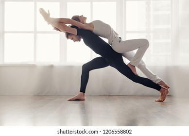 Fit young couple doing acro-yoga in modern studio