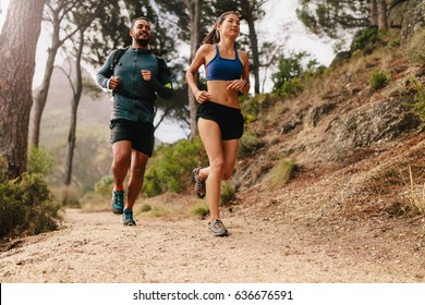 Fit young couple running on mountain trail in morning. Young man and woman jogging on country path.