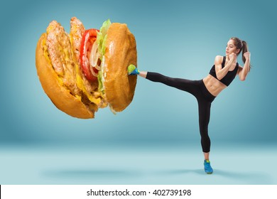 Fit, young, energetic woman boxing hamburger as unhealthy food