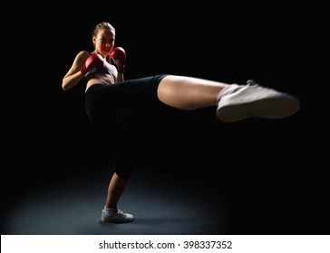 Fit, young, energetic woman kickboxing, black background