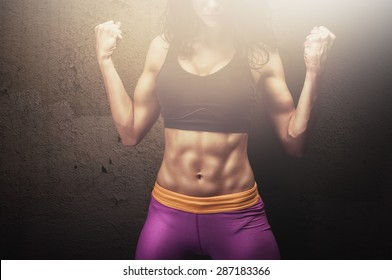 Fit young female fitness model posing and showing her muscular body with strong and tanned abdominal muscles in front of concrete wall