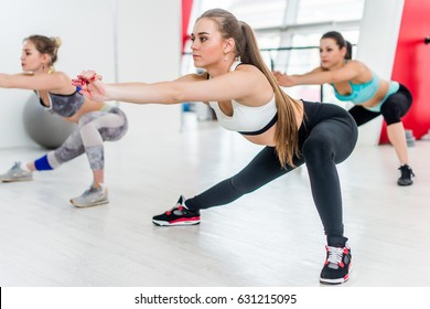 Fit young girls doing side lunges stretching their legs strengthening the quadriceps, glutes and hamstrings during group training indoors