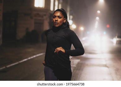 Fit young Indian woman in sportswear running along a road in the city at night illuminated by car lights