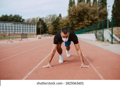 Fit young male caucasian athlete with face mask starting his sprint on an all-weather running track. Muscular athlete outdoors.  COVID - 19 coronavirus protection
