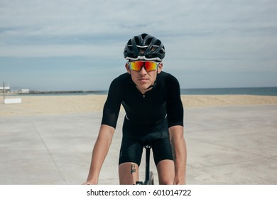 A fit young male cyclist riding near the beach on a cloud day