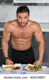 fit young man bodybuilder in the kitchen; animal versus plant proteins: plate with beef, eggs, salmon, cheese and chicken grill and another with nuts, mushrooms, broccoli, lentil, hummus and quinoa