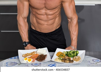 fit young man. bodybuilder in the kitchen; animal versus plant proteins: plate with beef, eggs, salmon, cheese and chicken grill and another with nuts, mushrooms, broccoli, lentil, hummus and quinoa