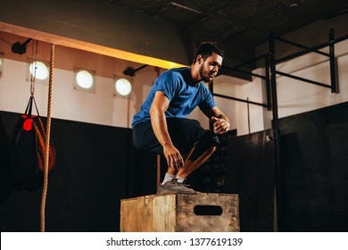 Fit young man doing a box jump exercise. Sports man doing a box squat at the gym