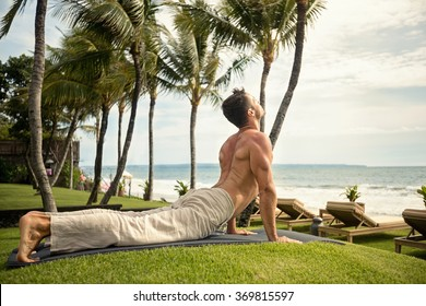 fit young man doing the cobra pose in nature near the ocean