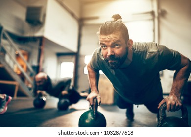 Fit young man doing pushups on dumbbells during an exercise class in a gym