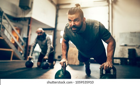 Fit young man doing pushups on dumbbells while working out during an exercise class in a gym