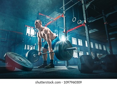 Fit young man lifting barbells working out at a gym. Sport, fitness, weightlifting, bodybuilding, training, athlete, workout exercises concept