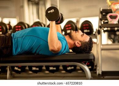 fit young man lifting dumbbells at the modern gym