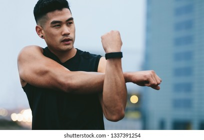 Fit young man with muscular build standing outside stretching hands and looking away. Asian fitness model doing warmup workout.
