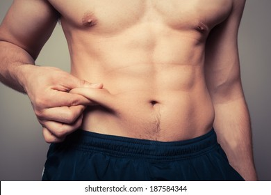 Fit young man pinching the fat on his stomach