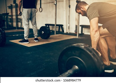 Fit young man preparing to lift heavy weights on a barbell during a workout session in a gym